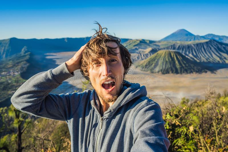 Young man meets the sunrise at the Bromo Tengger Semeru National Park on the Java Island, Indonesia. He enjoys. Magnificent view on the Bromo or Gunung Bromo on royalty free stock photography