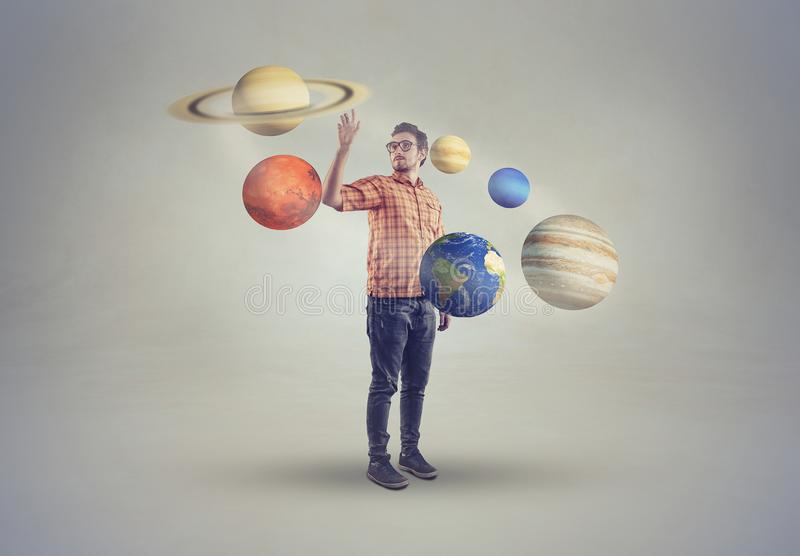 Young man in middle of solar system. Pointing to a planet stock photo