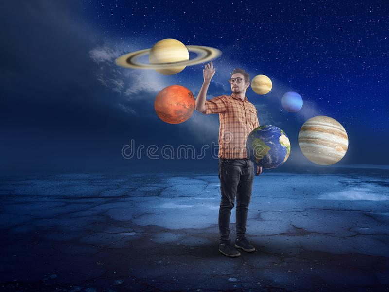 Young man in middle of solar system. Pointing to a planet into the night stock image