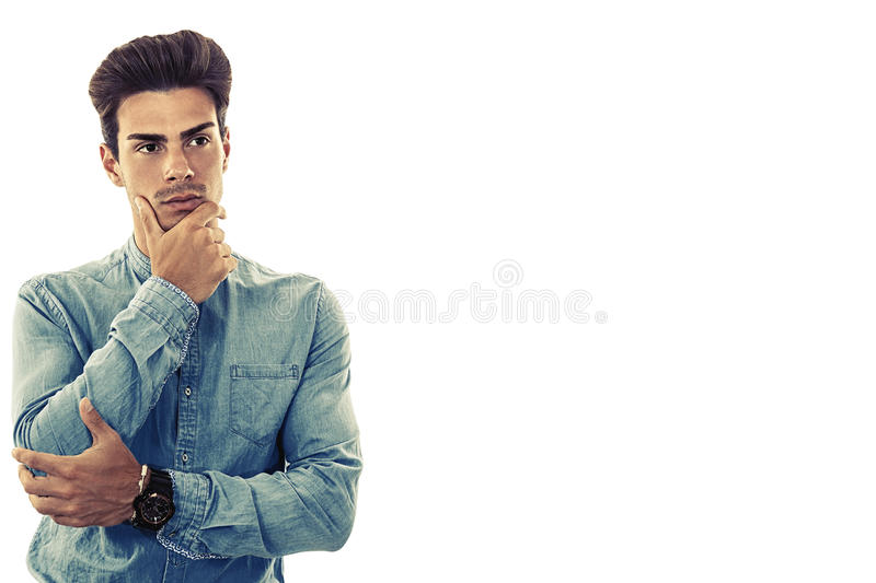 Young man model on white. Doubt and perplexity. Free empty side space. Doubt and perplexity. Young model man white background. Free empty space side. A nice boy royalty free stock photo
