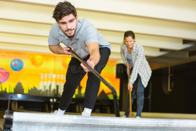 Young man with mop cleaning floor in bowling lobby royalty free stock images