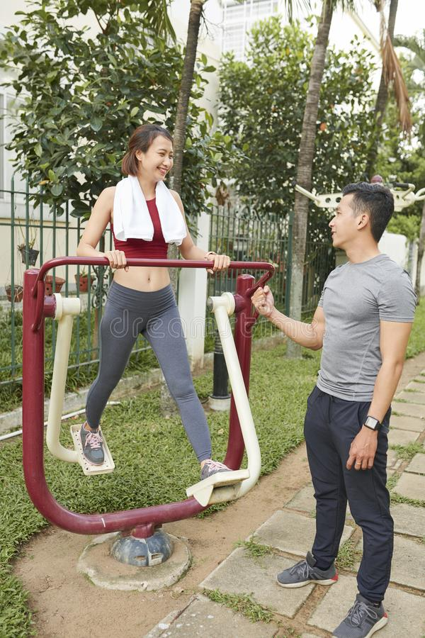 Young man motivating his exercising girlfriend stock photography