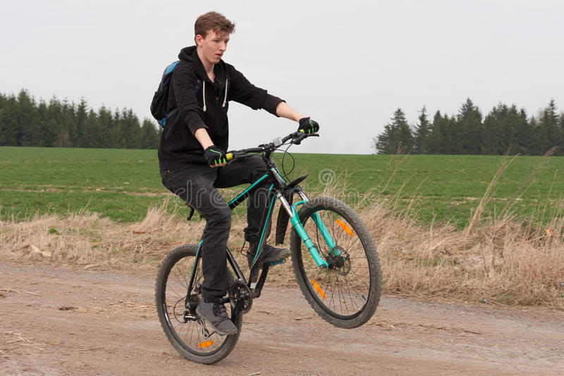 Young man on mountain bike jumps on path royalty free stock photography