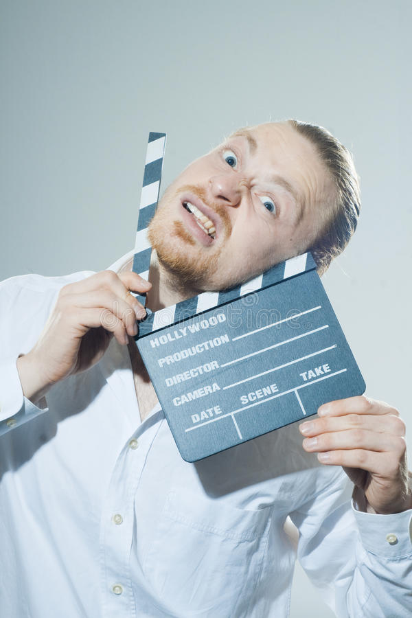 Young man with movie clapper. In white shirt royalty free stock photo