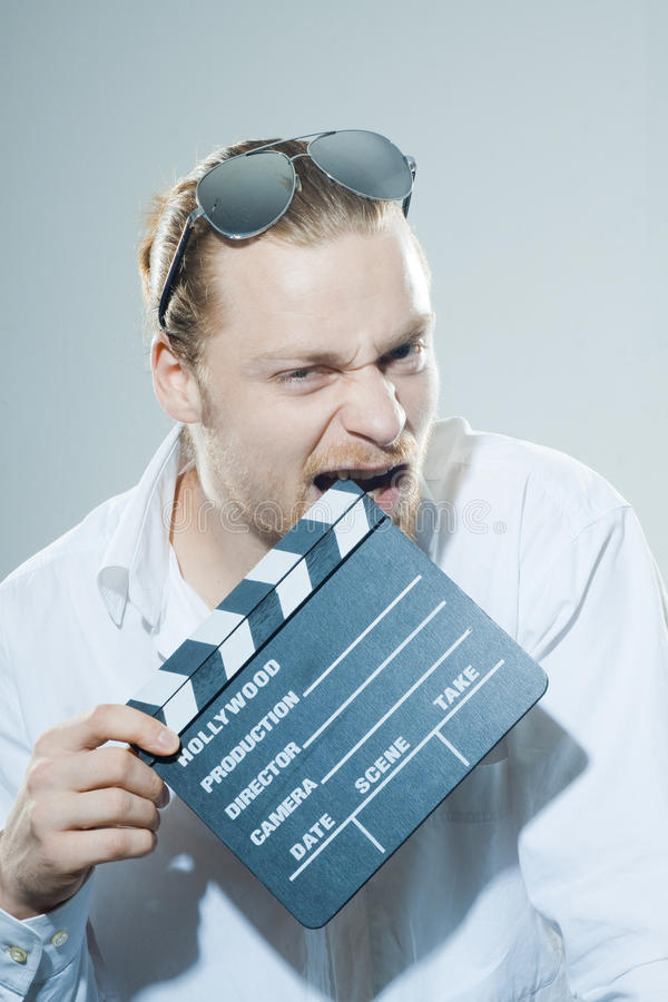 Young man with movie clapper. In white shirt royalty free stock photography