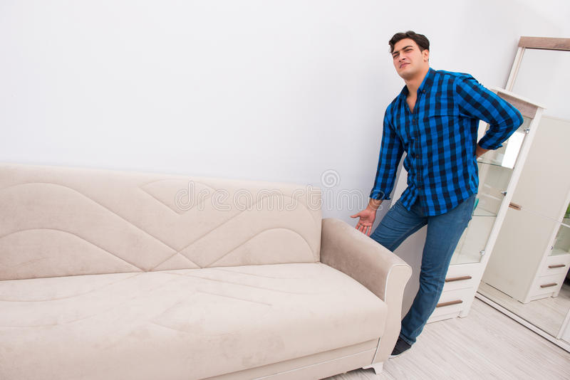 The young man moving sofa couch. Young man moving sofa couch royalty free stock photography