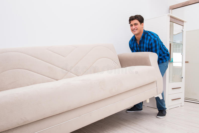 The young man moving sofa couch. Young man moving sofa couch stock photography