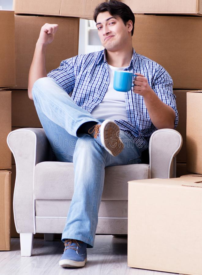 Young man moving in to new house with boxes. The young man moving in to new house with boxes royalty free stock photos