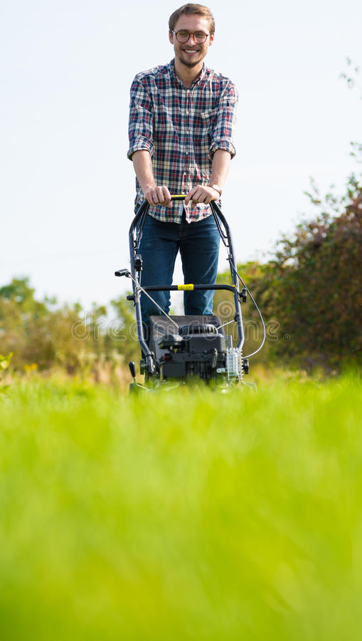 Man Cutting Grass In His Garden Stock Image - Image of