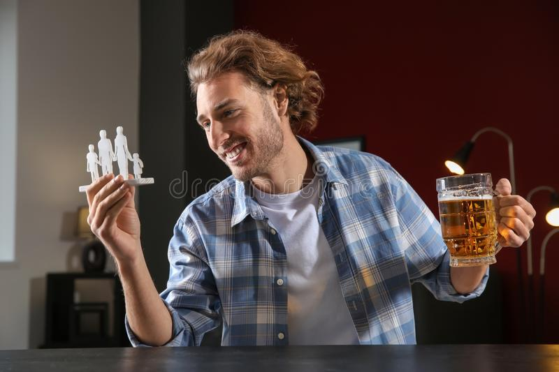 Young man with mug of beer and figure at table. Concept of choice between alcohol and family royalty free stock photography