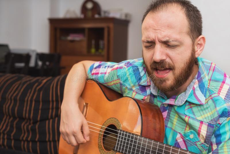 Young man musician playing acoustic guitar stock photo