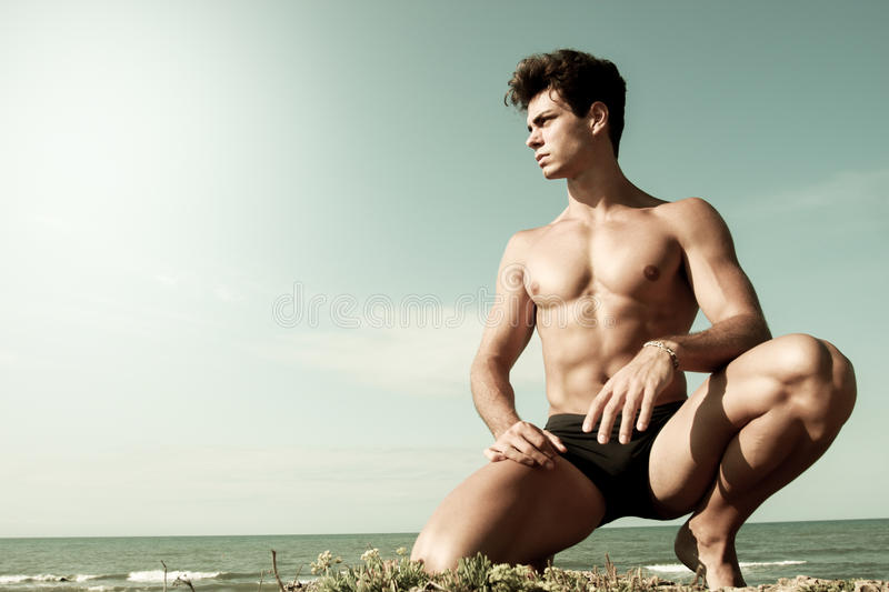 Young man naked on his knees. Sea and sky behind. A young man with a beautiful body is on his knees with the sea behind. Intense light and color antiqued royalty free stock image
