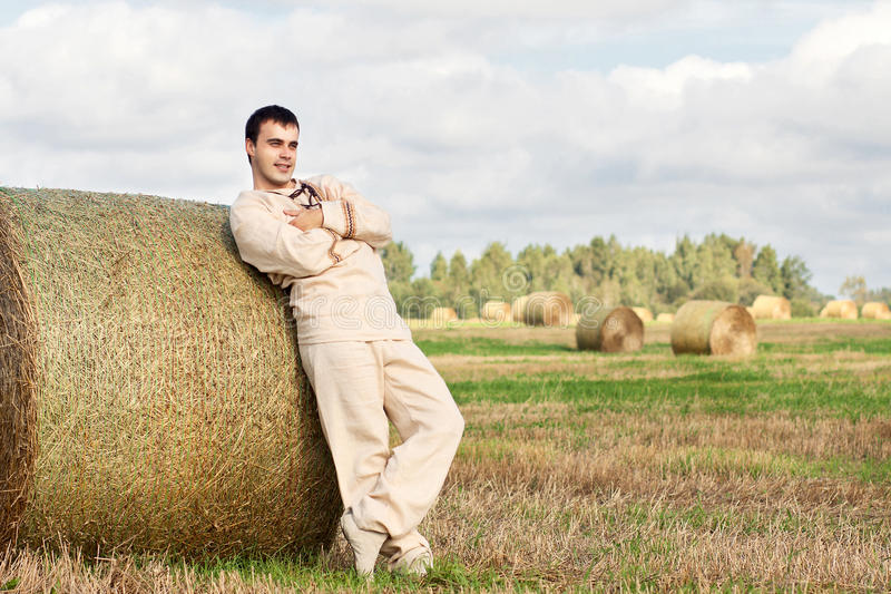Young man in national rustic costume. Resting on a haystack stock photography