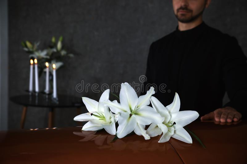 Young man near casket with white lilies in funeral royalty free stock photography