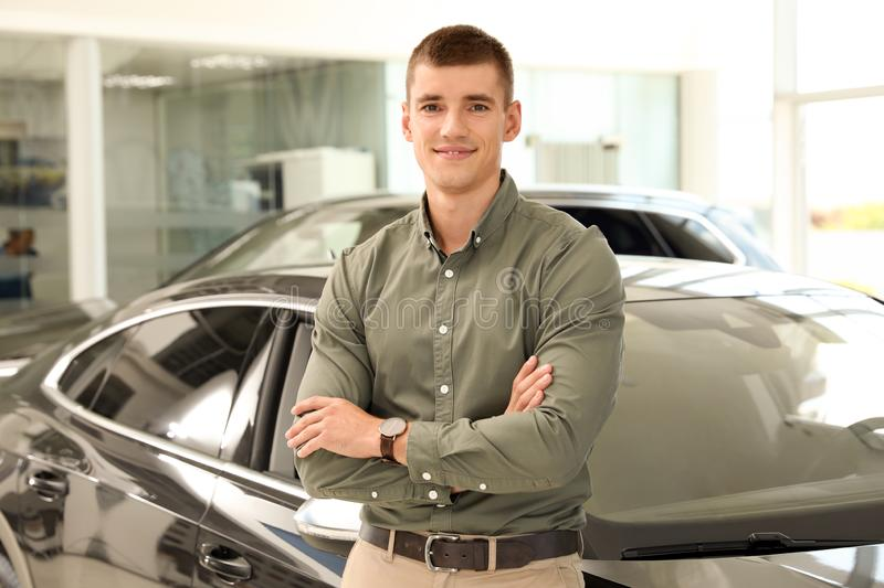 Young man near new car in  auto dealership. Young man near new car in modern auto dealership stock photos