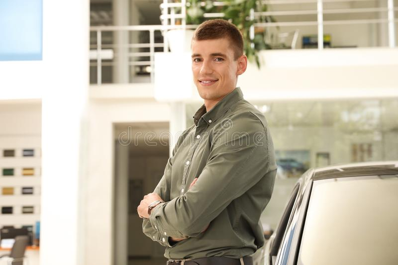 Young man near new car in  auto dealership. Young man near new car in modern auto dealership stock photography