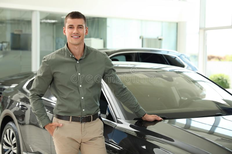Young man near new car in modern auto dealership. Space for text stock photography