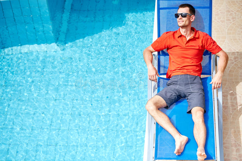 Young man near the pool. Young man relaxing on the chaise-longue near the pool. man wearing in red polo shirt and sunglass royalty free stock photography
