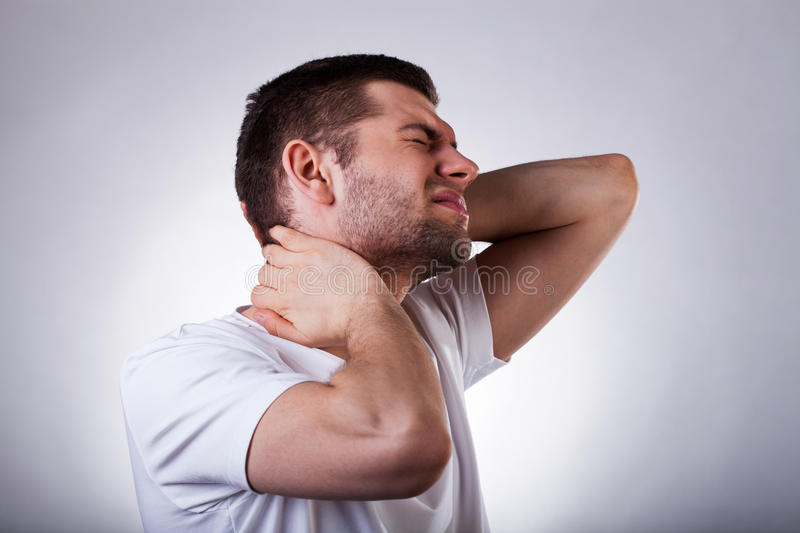 Young man with neck ache. Young exhausted man with strong neck ache isolated on white background stock photos