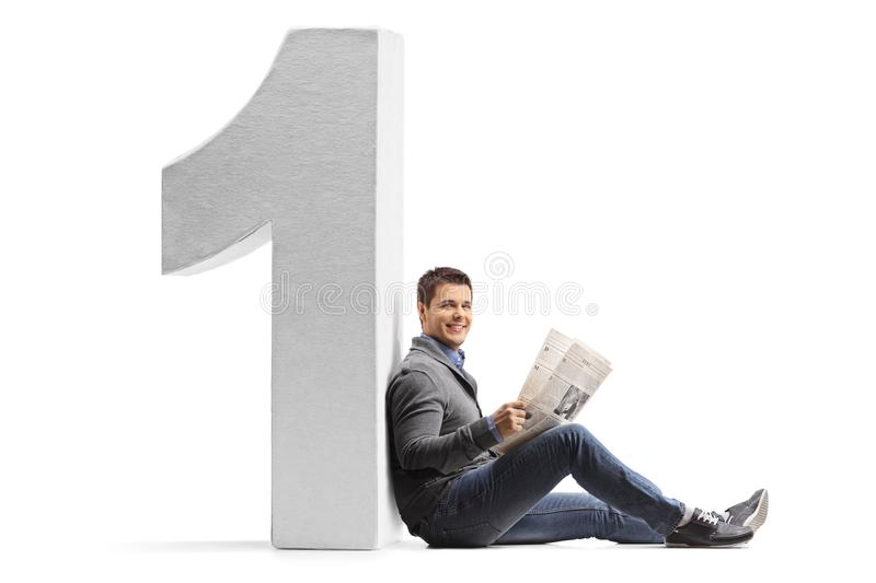 Young man with a newspaper leaning against a cardboard number on royalty free stock photography