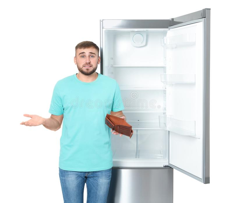 Young man with no money in wallet near empty refrigerator on white background royalty free stock image