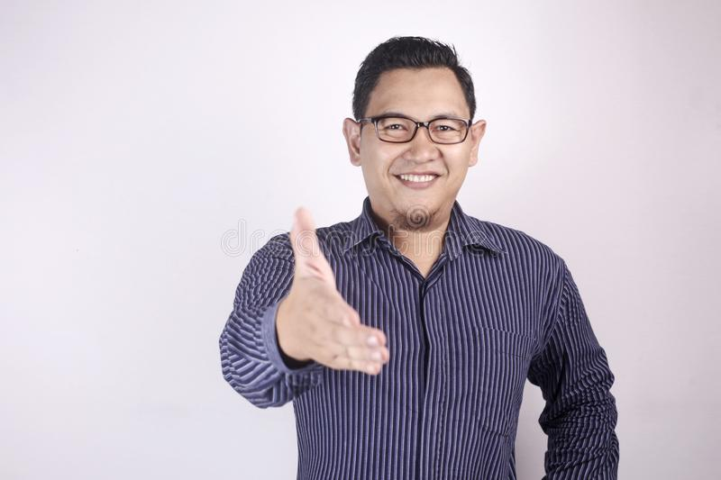 Young Man Offering Handshake. Portrait of young Asian man offering handshake and smiling against white background, selective  image, deal agreement concept blue stock photography