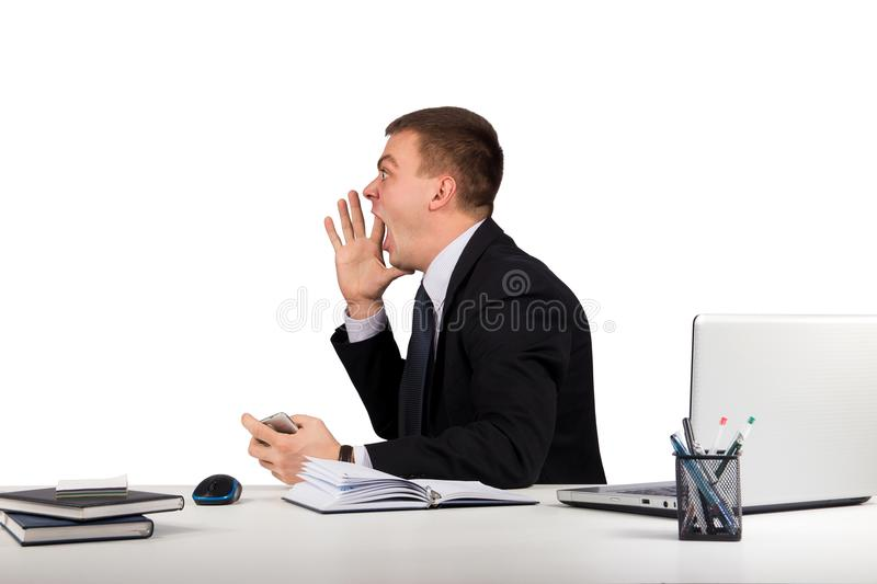 Young man in office shouting with hands cupped to his mouth isolated on white background royalty free stock images