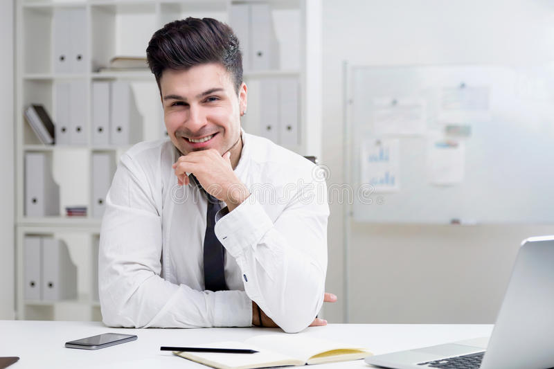 Young man at office table stock photo