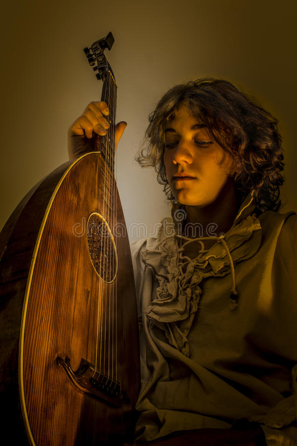 Young Man with Old Oud Guitar Lute. Young man with long blond hair sitting in dark environment and hold in His Hands an Old Oud, Guitar Lute and looking at it royalty free stock image
