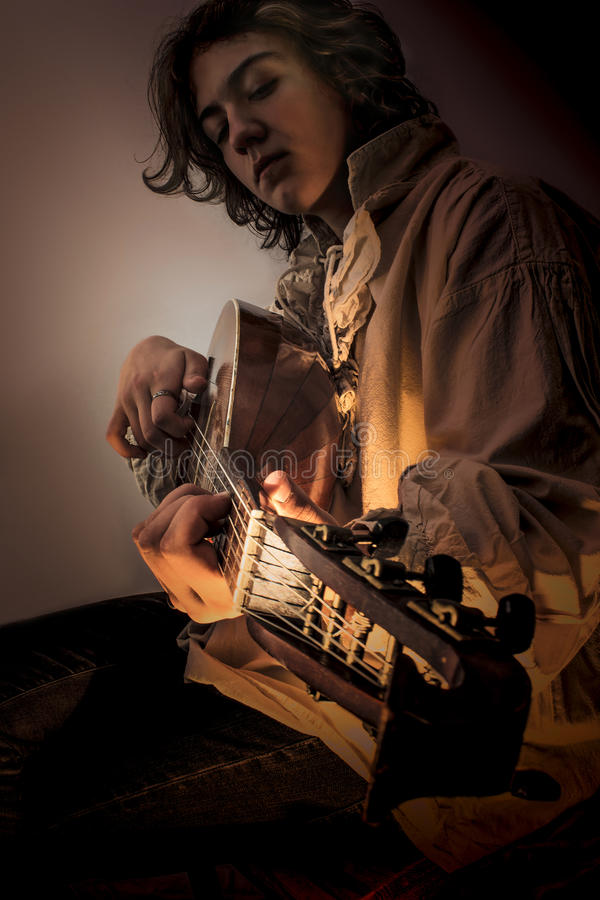 Young Man with Old Oud Guitar Lute. Young man with long blond hair sitting in dark environment and playing an Old Oud, Guitar Lute and looking at it. He is stock image