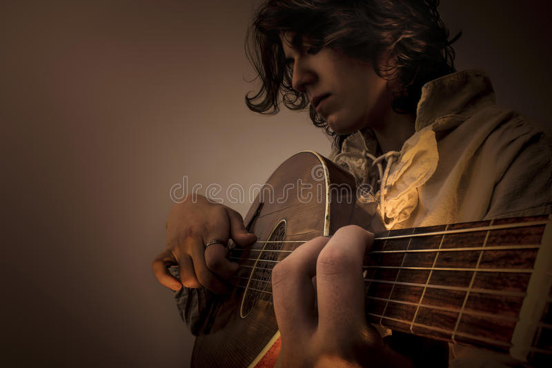 Young Man with Old Oud Guitar Lute. Young man with long blond hair sitting in dark environment and playing an Old Oud, Guitar Lute and looking at it. He is royalty free stock photo