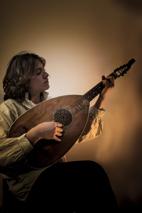 Young Man with Old Oud Guitar Lute. Young man with long blond hair sitting in dark environment and playing an Old Oud, Guitar Lute and looking at it. He is royalty free stock images