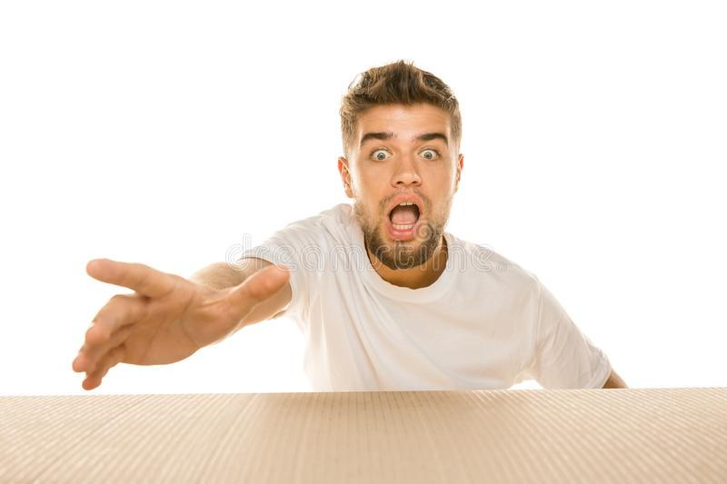 Young man opening the biggest postal package isolated on white. Young astonished man opening the biggest postal package isolated on white. Shocked male model on royalty free stock images