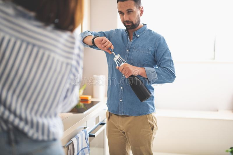 Young man opening bottle of wine while looking at lady royalty free stock images