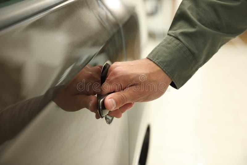 Young man opening car door in  auto dealership, closeup. Young man opening car door in modern auto dealership, closeup stock photography