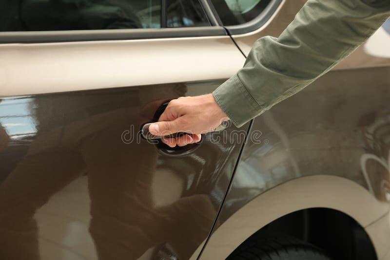 Young man opening car door in modern auto dealership. Closeup royalty free stock image