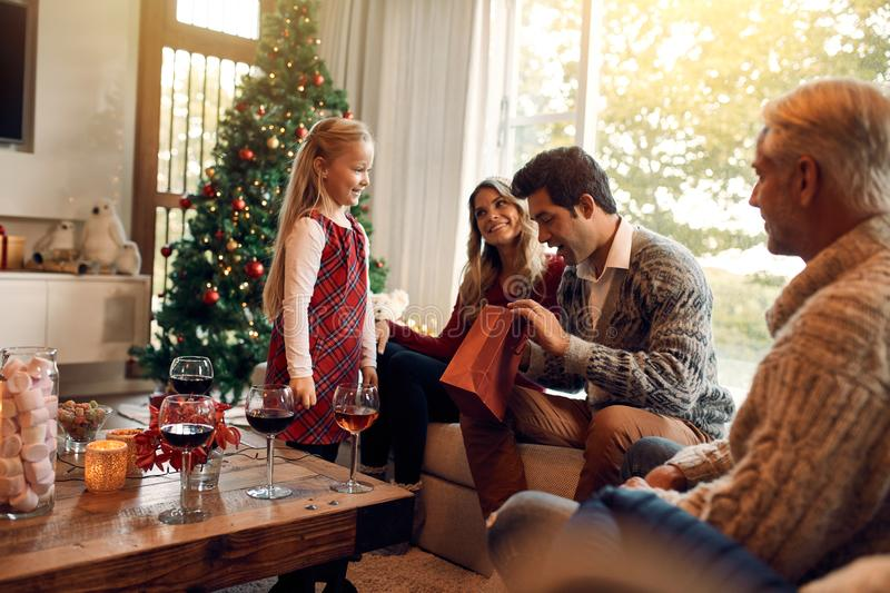 Young man opening christmas gifts from her daughter. Young men opening christmas gifts from her daughter. Caucasian family sitting together in living room on a royalty free stock image