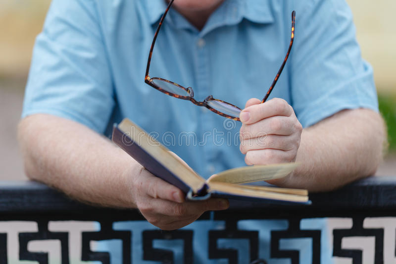 Young man opening and reading a book, close up. stock images