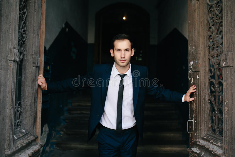 Young man opens an old door. Handsome young man opens an old door stock photography