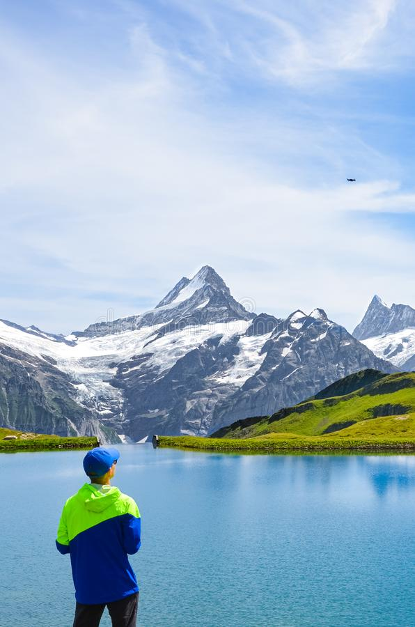 Young man operating the flying drone over amazing Bachalpsee in the Swiss Alps. Drone cameras are used for aerial photography and royalty free stock photos