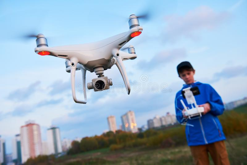Young man operating of flying drone at sunset. Man operating drone flying or hovering by remote control in sunset royalty free stock image