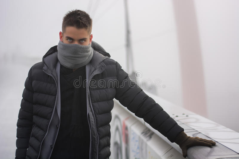 Young man outdoor in winter fashion. Young man in winter fashion standing outdoors in a warm overcoat and gloves with his grey scarf wound round the lower half royalty free stock photography