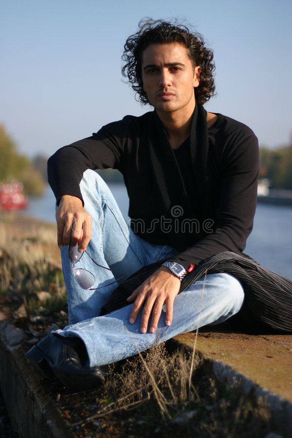 Young man outdoors. Young handsome serious man outdoors royalty free stock photography