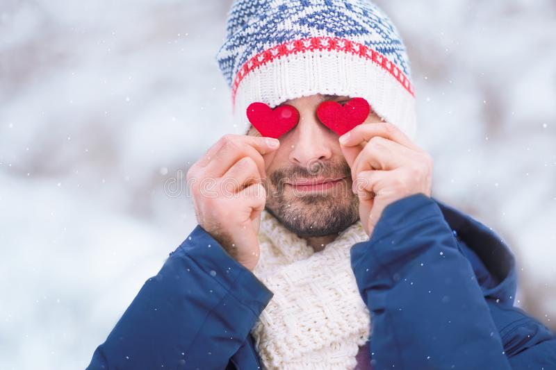 Young man outdoors with two hearts at his eyes royalty free stock image