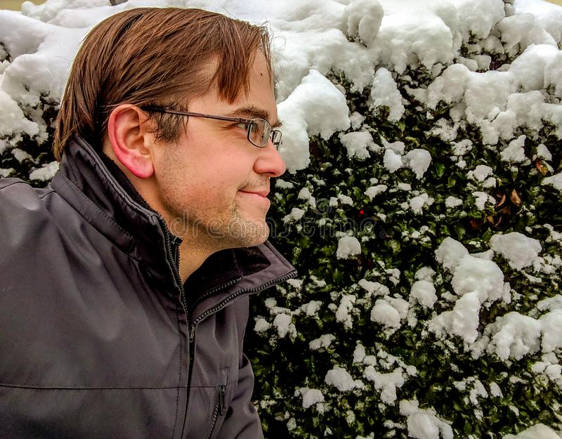 Young Man Outdoors in Wintertime with Snow Covered Holly Bush in Background royalty free stock photos