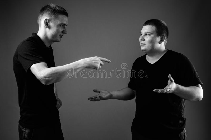 Young man and overweight young man in black and white. Studio shot of young men and overweight young men together against black background in black and white royalty free stock image