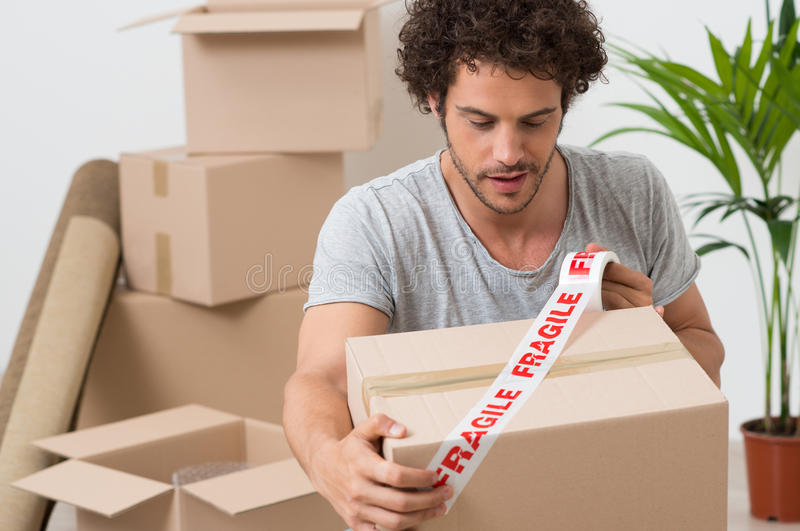 Young Man Packing Cardboard Box royalty free stock photography