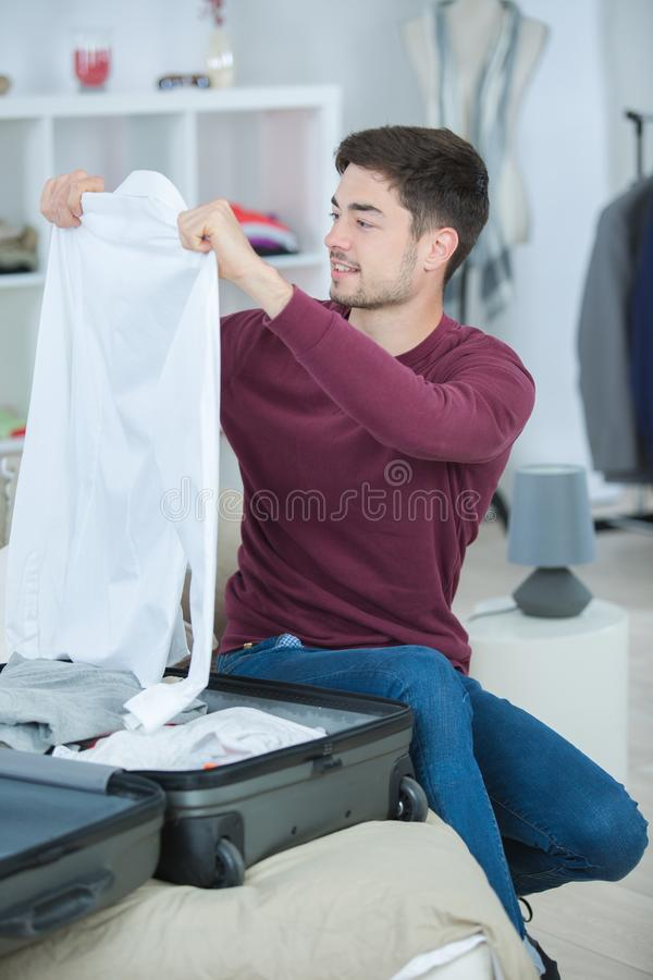Young man packing bag and preparing for traveling royalty free stock image