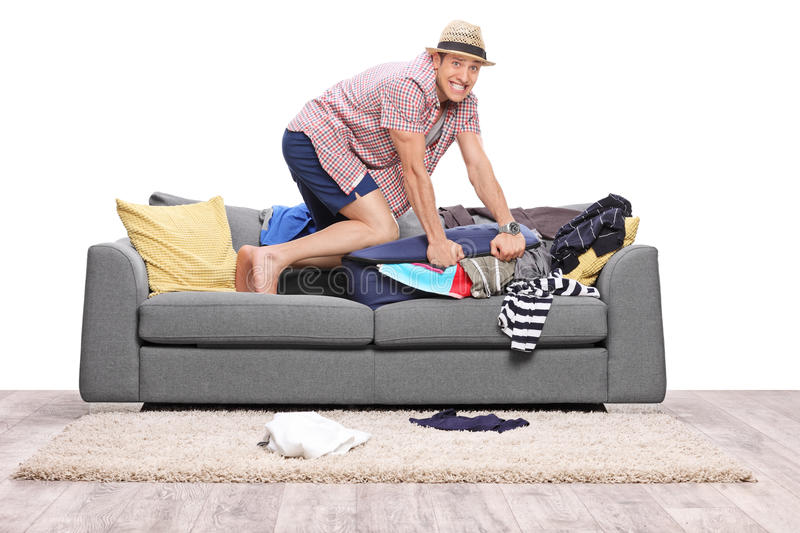 Young man packing a lot of clothes into one suitcase. And looking at the camera isolated on white background stock photo