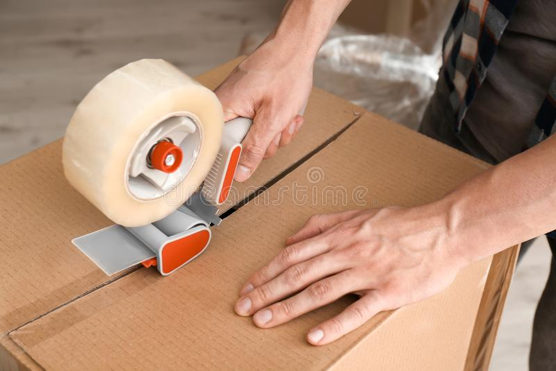 Young man packing moving box indoors royalty free stock photography
